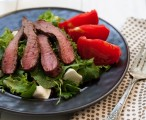 Tasty greens topped with thinly sliced steak, surrounded by tomatoes and Italian cheese.