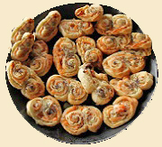 This appetizer is shaped like palmiers but is savory, rather than sweet in taste. The puff pastry rolled up and baked with brie, onions and caraway is delicious.