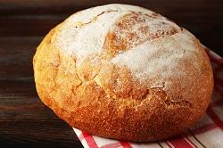 Fresh bread on napkin on wooden background