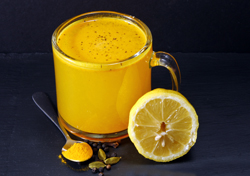 Spicy healthy Haldi or Turmeric, lemon and pepper antioxidant drink with lemon on a moody background.
