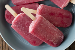 Homemade Raspberry and vanilla ice pops on a rustic wood background. Berry icecream popsicles. Summer food.