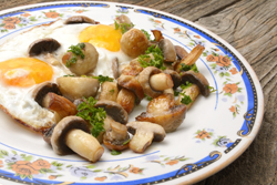 fried eggs on rustic table with mushrooms