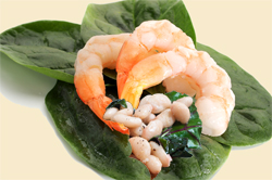 Close-up image of shrimps with spinach leaves