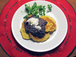 Corn and black beans are a great duo. These corn fritters topped with a spicy black bean mixture and sour cream make a quick and scrumptious dinner.